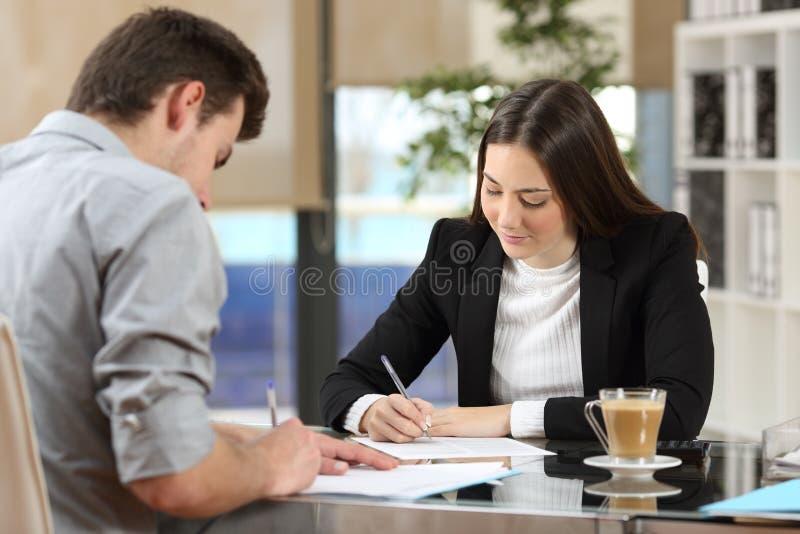 Persone di affari che firmano i contratti dopo l'affare immagini stock