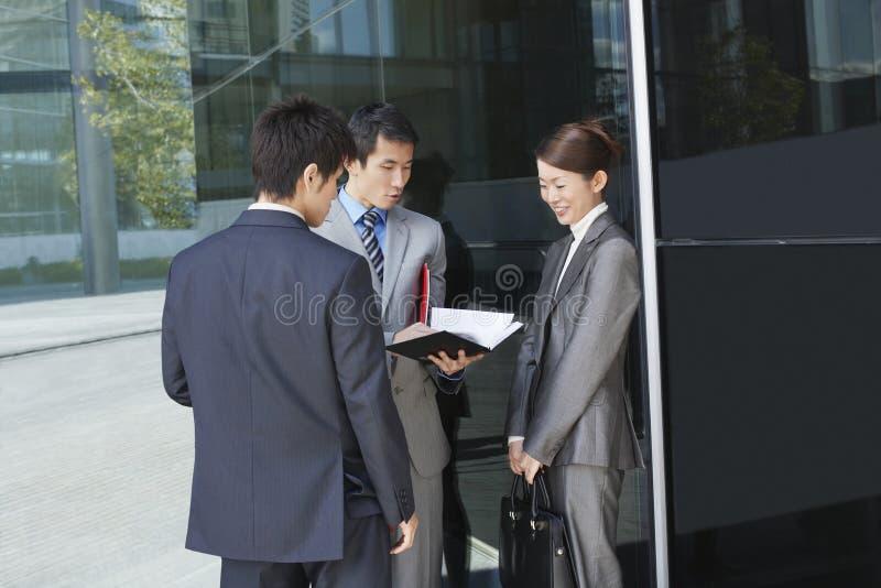 Persone di affari che guardano attraverso i documenti all'aperto immagini stock libere da diritti