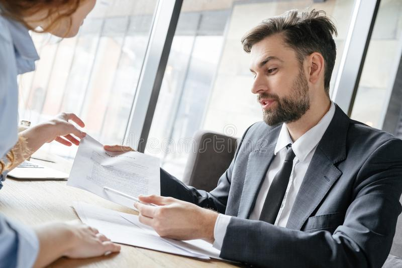 Persone di affari che hanno pranzo di lavoro all'uomo di seduta del ristorante che spiega i termini di accordo che sorridono alle immagine stock