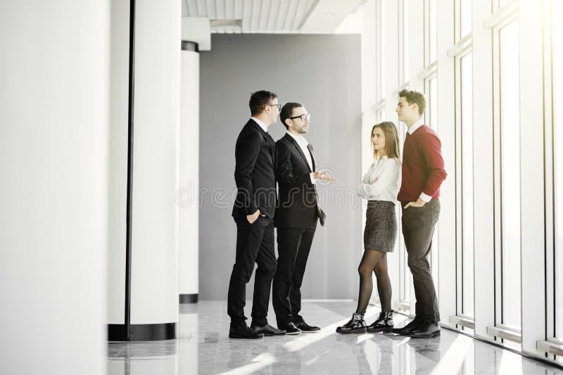 Persone di affari che hanno riunione informale in ufficio moderno sul fondo delle finestre immagine stock
