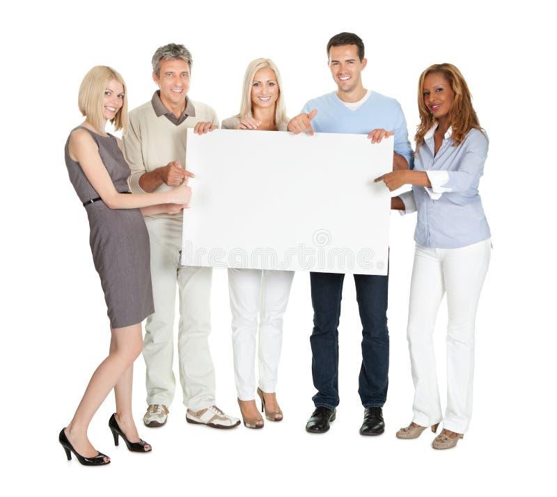 Persone di affari che mostrano un bordo in bianco fotografia stock libera da diritti