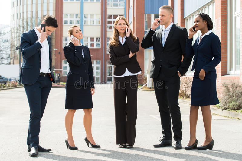 Persone di affari che parlano sui telefoni cellulari fotografia stock