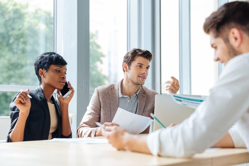 Persone di affari che parlano sul telefono cellulare e che lavorano insieme nell'ufficio immagine stock libera da diritti