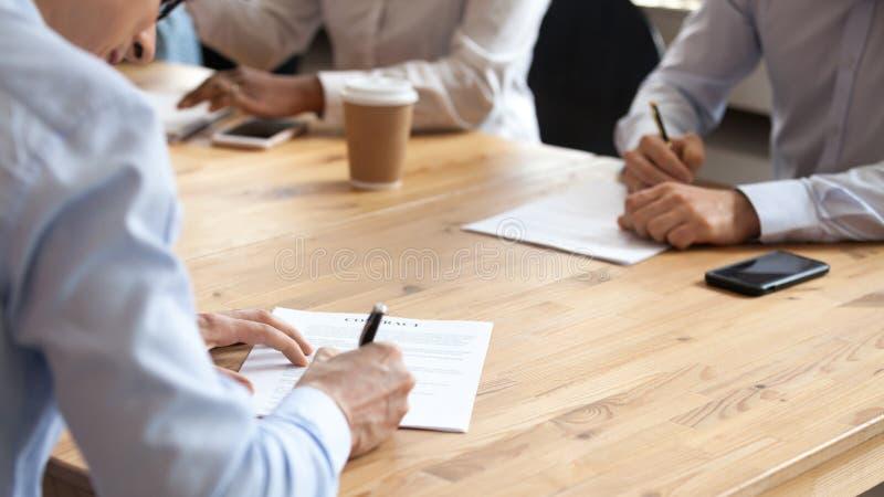 Persone di affari che si siedono alla tavola durante la riunione del contratto di firma raggiunto di accordo fotografia stock libera da diritti
