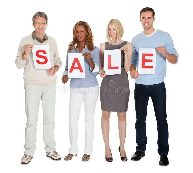 Persone di affari che tengono Libro Bianco con la vendita di parola immagini stock