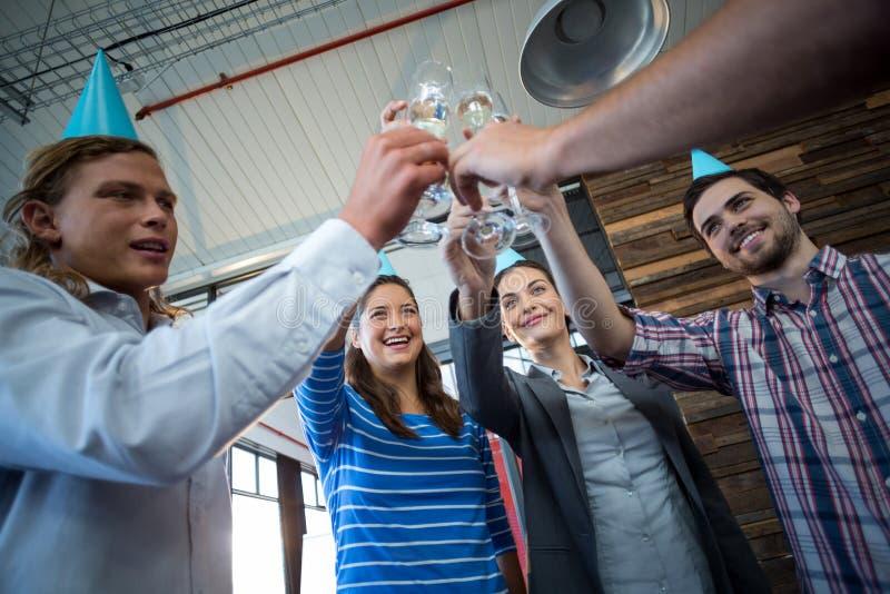 Persone di affari che tostano i bicchieri di vino immagine stock