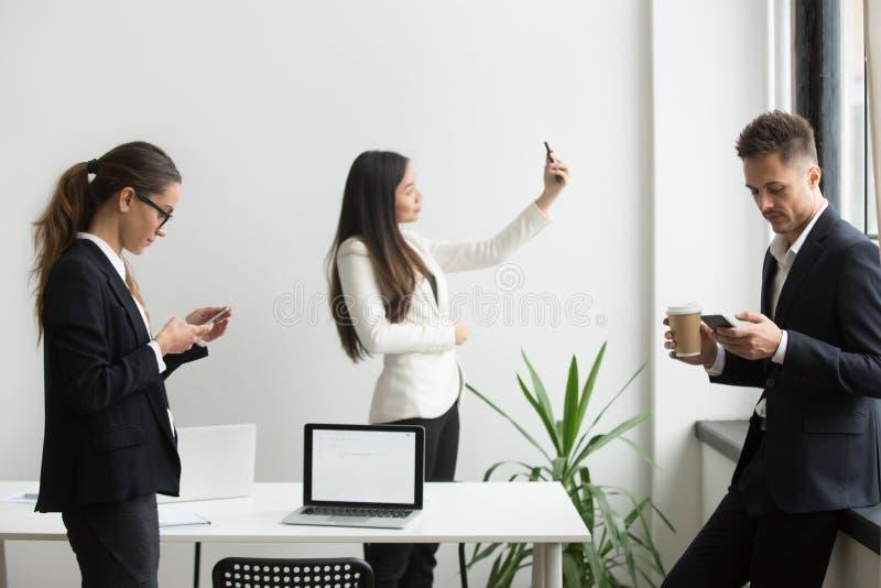 Persone di affari che utilizzano mandare un sms degli smartphones, prendente selfie in offic fotografia stock libera da diritti