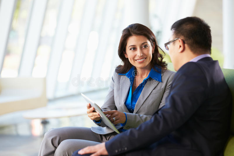 Persone di affari con la compressa di Digital che si siede nell'ufficio moderno immagine stock