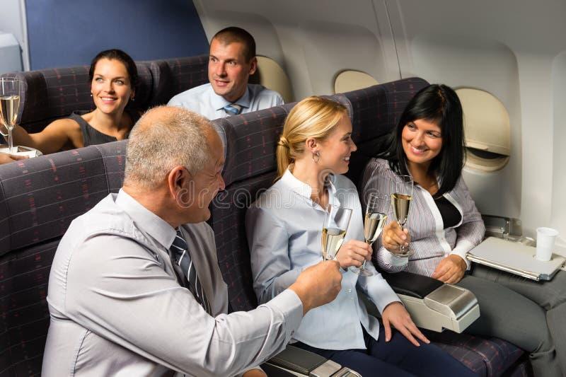 Persone di affari della cabina dell'aeroplano che tostano champagne immagini stock libere da diritti