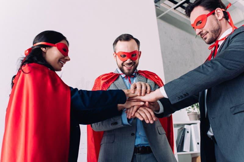 persone di affari eccellenti felici nelle maschere e capi che un le mani immagine stock