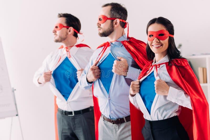 persone di affari eccellenti nelle maschere e capi che mostrano le camice blu fotografia stock