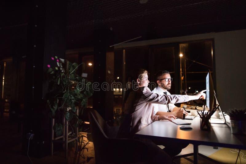 Persone di affari nell'ufficio alla notte che lavora tardi fotografie stock libere da diritti