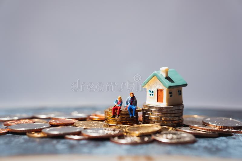 Persone in miniatura, uomini e donne seduti su una pila di monete usando come concetto di business e di successo per la vita fotografie stock libere da diritti