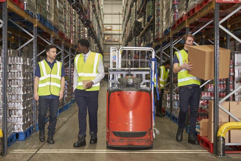 Personeel aan het werk in de doorgang van een bezig distributiepakhuis stock afbeelding