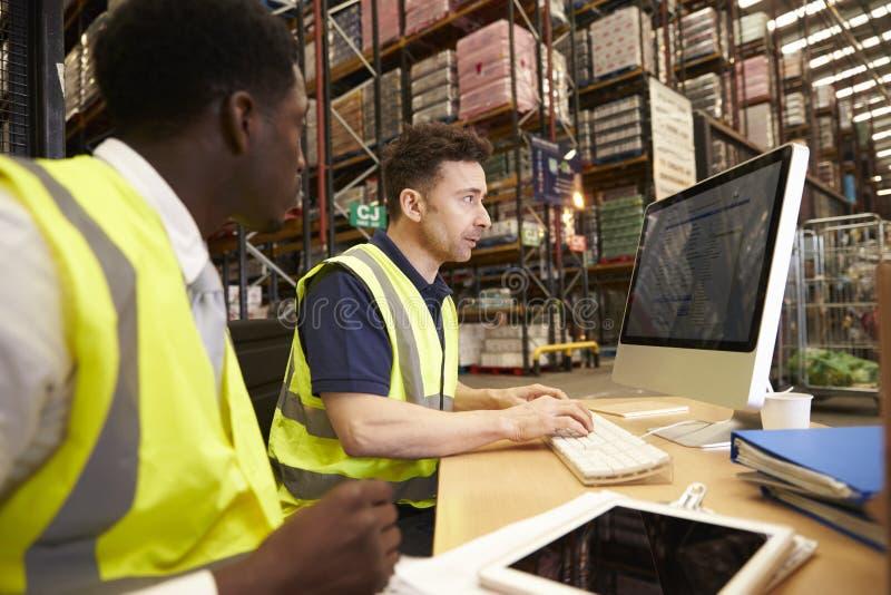 Personeel die in bureau ter plaatse bij een distributiepakhuis werken royalty-vrije stock foto