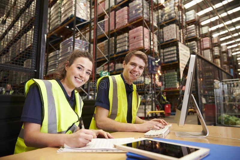 Personeel in het bureau van een distributiepakhuis, aan camera royalty-vrije stock afbeeldingen