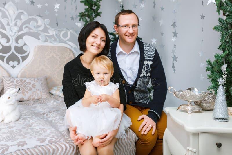 Personen der Weihnachtsglückliche dreiköpfigen Familie, die auf dem Bett des weißen Schlafzimmerhintergrundes sitzen stockbild