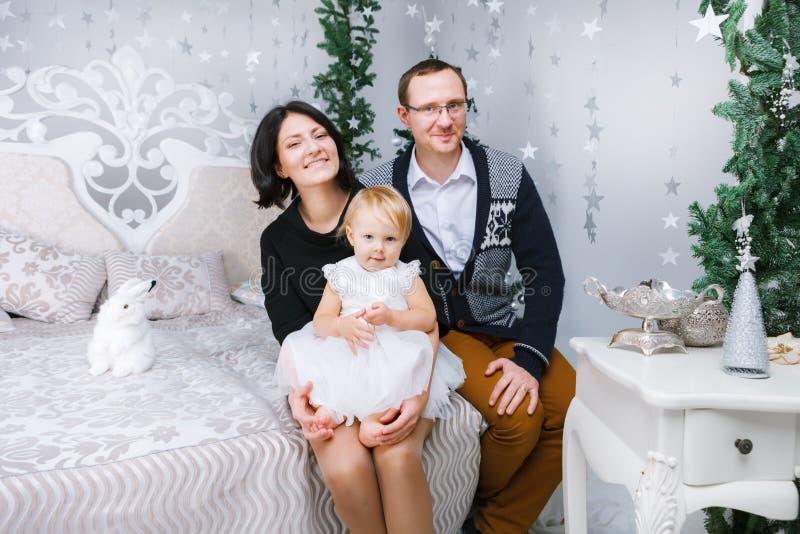 Personen der Weihnachtsglückliche dreiköpfigen Familie, die auf dem Bett des weißen Schlafzimmerhintergrundes sitzen lizenzfreie stockfotografie