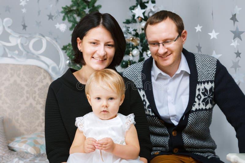Personen der Weihnachtsglückliche dreiköpfigen Familie, die auf dem Bett des weißen Schlafzimmerhintergrundes sitzen stockfotografie