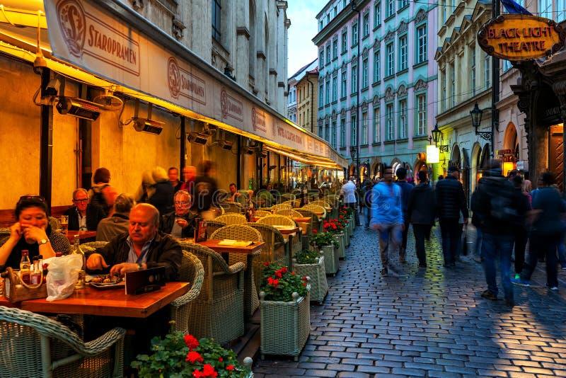 Personen, die in einem Restaurant im Freien neben der Kopfsteinpflasterstraße in Prag sitzen lizenzfreies stockbild