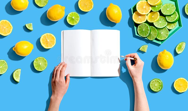 Personen, die in Notebooks mit Zitronen und Limetten schreiben lizenzfreie stockfotografie