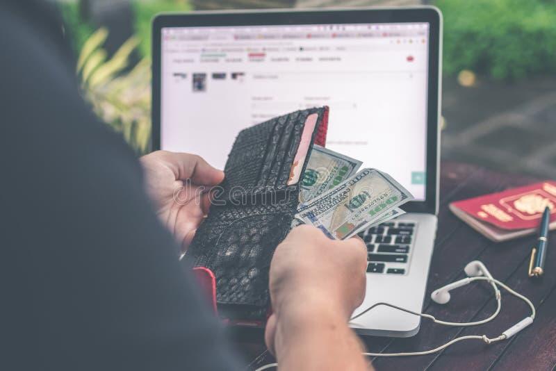 Personen-Holding 10 US-Dollar Banknote vor Grau und schwarzer Laptop-Computer stockbild