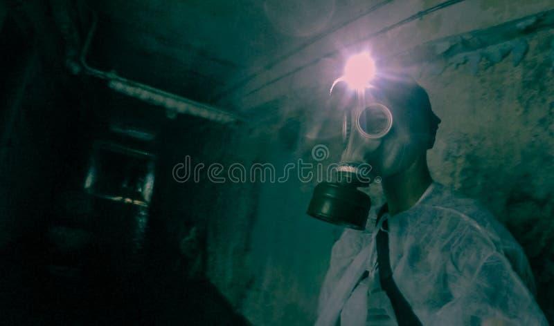 Personen med gasmasken undersöker den radioaktiva fängelsehålan i Pripyat, den Tjernobyl zonen royaltyfria foton