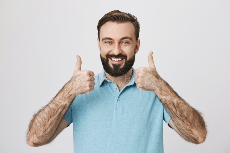 Personen med gulliga skägg- och mustaschtummar visar upp till hans positiva svar som står den near vita väggen Moget bära för man arkivbild
