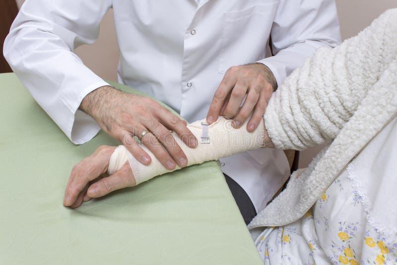 Personen med paramedicinsk utbildning i ett vitt lag avslutar till pålagt mycket gammal kvinnas dressing royaltyfria foton