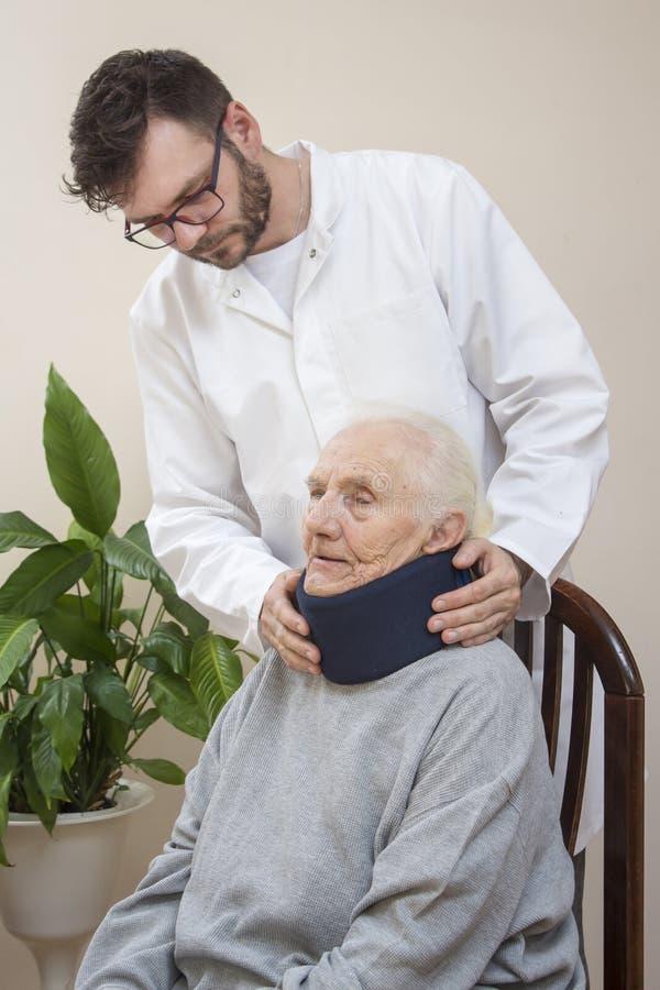 Personen med paramedicinsk utbildning sätter en ortopedisk krage på halsen av en mycket gammal kvinna royaltyfria bilder