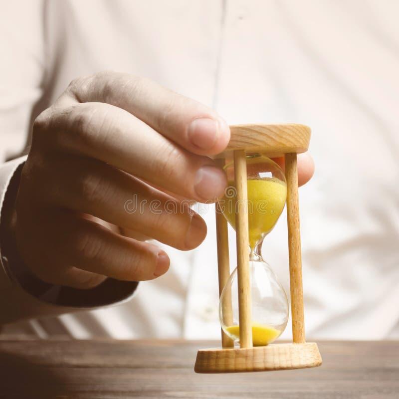 Personen rymmer ett timglas i hans händer Tre personer bak deras baksidor kugghjul, lagarbete inom f?retaget Logistik processeffe royaltyfri foto
