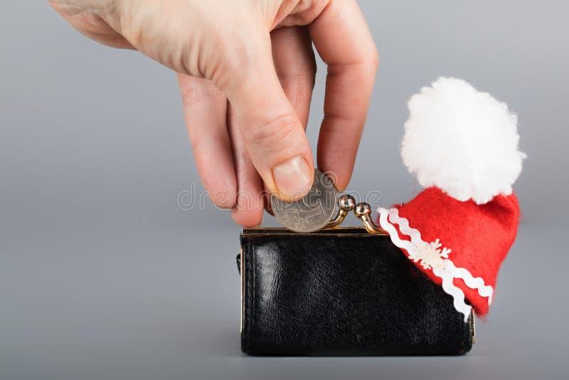 Personen sätter mynt av fem ryska rubel i svarta purs för ett läder royaltyfri foto