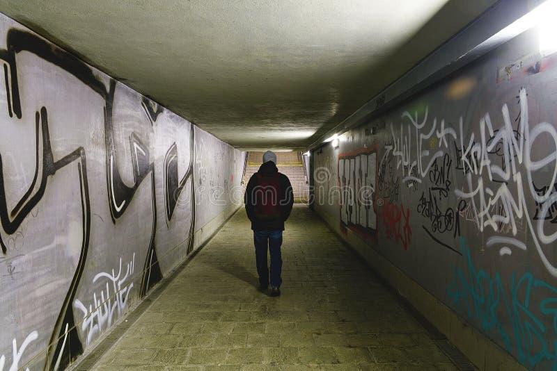 Personen som går i gångtunnelgångtunnel - tänd på slutet av tunnelen - man att gå bara i ett potentiellt farligt ställe royaltyfria foton