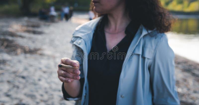 Personen som utomhus r?ker marijuanaskarven royaltyfri fotografi