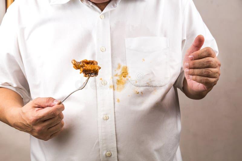 Personen spillde oavsiktligt curryfläck på den vita skjortan royaltyfria foton