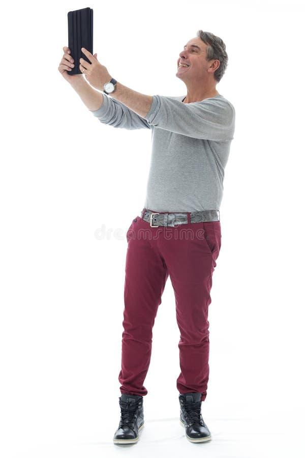 Personen tar en selfie genom att använda en digital minnestavla Gråhårig man oss royaltyfri foto