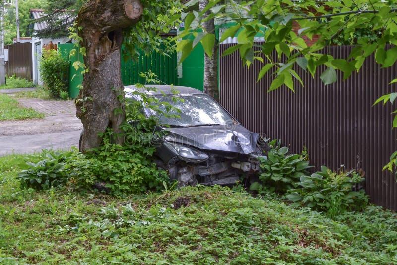 Personenauto in een ongeval in de struiken dichtbij de omheining wordt verpletterd die royalty-vrije stock fotografie