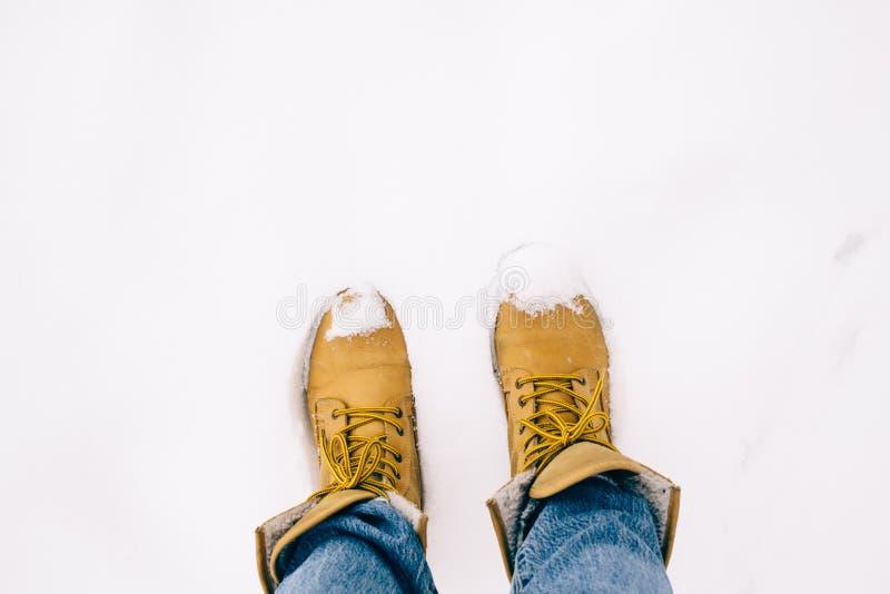 Personenbeine in den gelben Stiefeln mit Blue Jeans auf dem Schnee, Winter kommt stockfoto