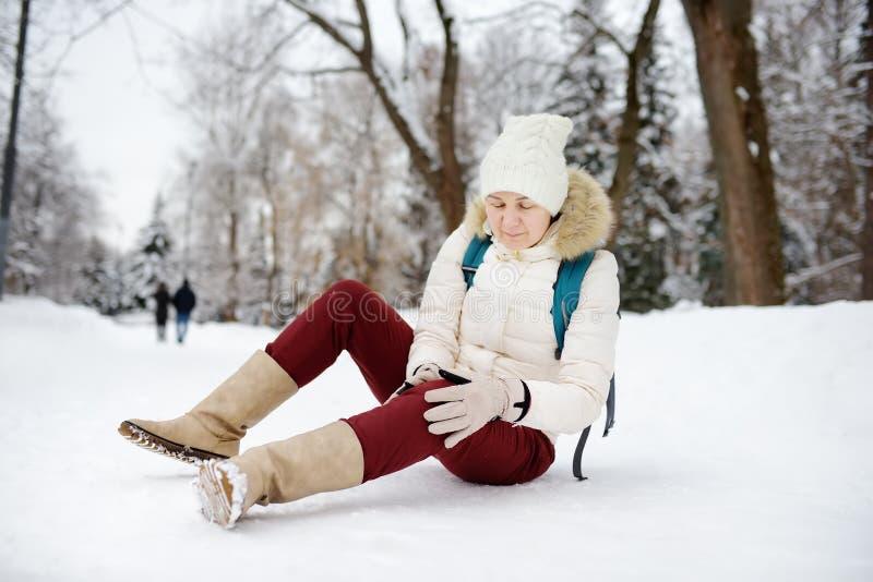 Personens hälsa i vinterparken Kvinnlig glidning på isberget, fall, skada knä och sittande i snön royaltyfri foto