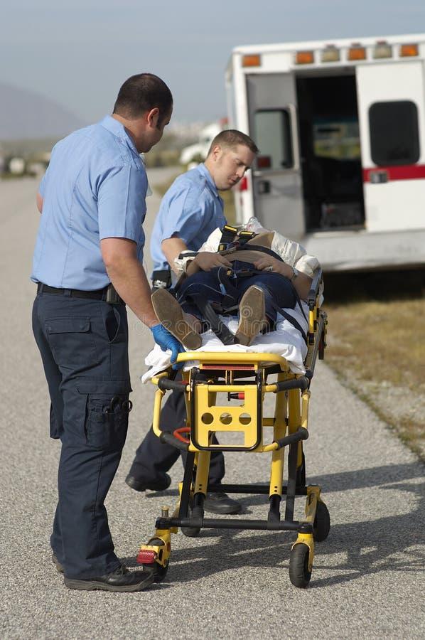 Personer med paramedicinsk utbildning som bär offret på båren arkivfoto