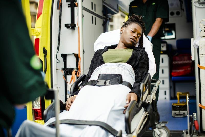 Personer med paramedicinsk utbildning som flyttar en patient på en bår in i en ambulans arkivbild