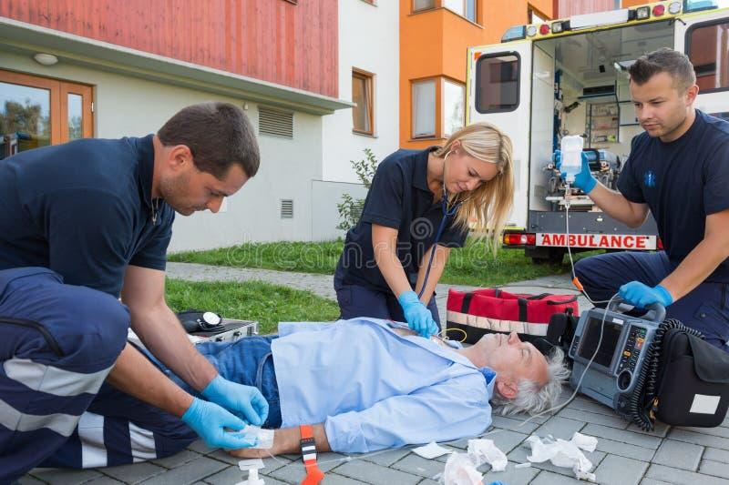 Personer med paramedicinsk utbildning som ger firstaid till den medvetslösa patienten royaltyfria bilder