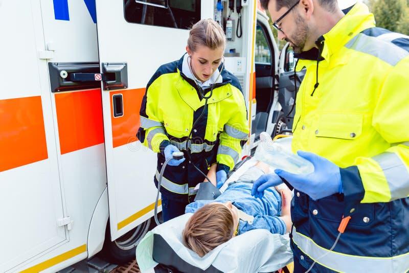 Personer med paramedicinsk utbildning som mäter blodtryck av den sårade pojken arkivbild