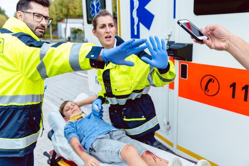 Personer med paramedicinsk utbildning som slåss folk som försöker att göra foto av olycka royaltyfria bilder