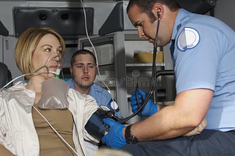 Personer med paramedicinsk utbildning som tar omsorg av offret i ambulans royaltyfri fotografi