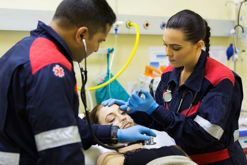 Personer med paramedicinsk utbildning som undersöker patienten royaltyfri fotografi