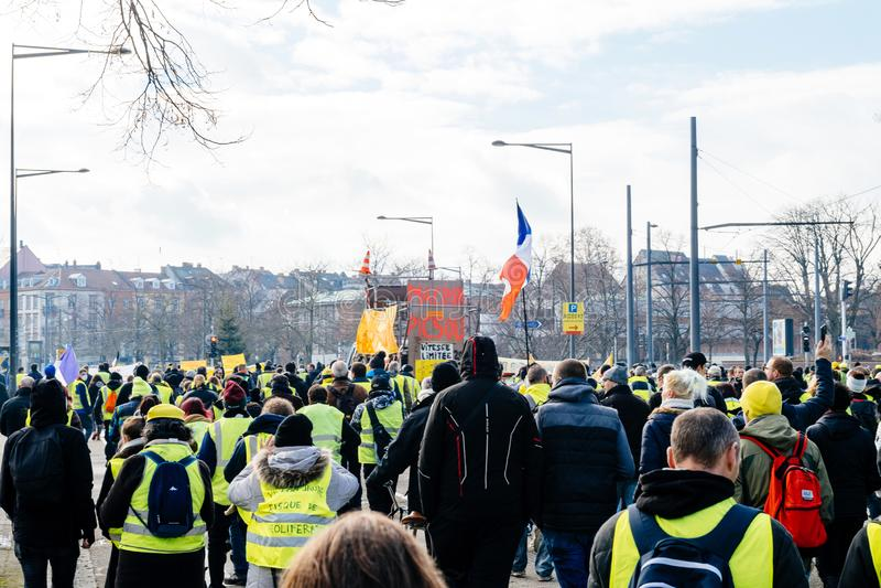 Personer som protesterar med palcardgirigbuken McDuck jämbördiga Emmanuel Macron arkivfoton