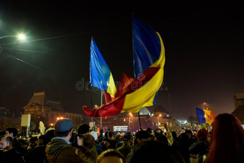 Personer som protesterar som flyger rumänska flaggor royaltyfri fotografi