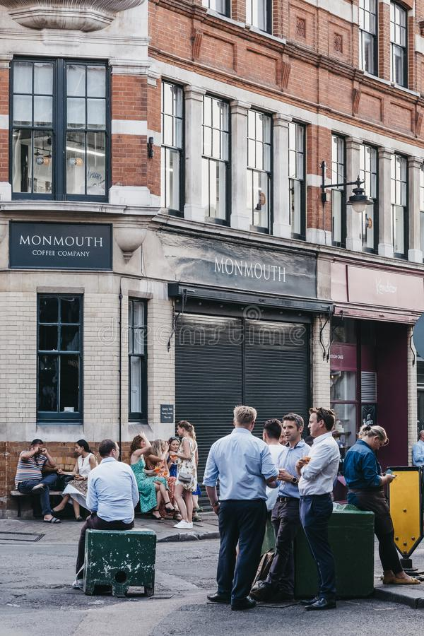 Personer som står och dricker på en gata utanför kaféer och pubar på Borough Market, London, Förenade kungariket royaltyfria foton
