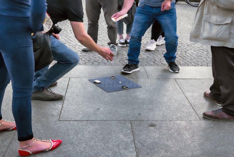 141/5000 personer står offentligt i mitt av gatan och försöket för att erbjuda deras olagliga lek av boll-bollen till argelosetur royaltyfria foton